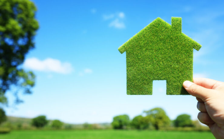 Green ecological house in empty field